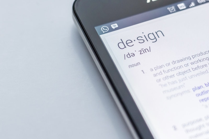 "photo of smartphone with definition of ""design"" on its screen"