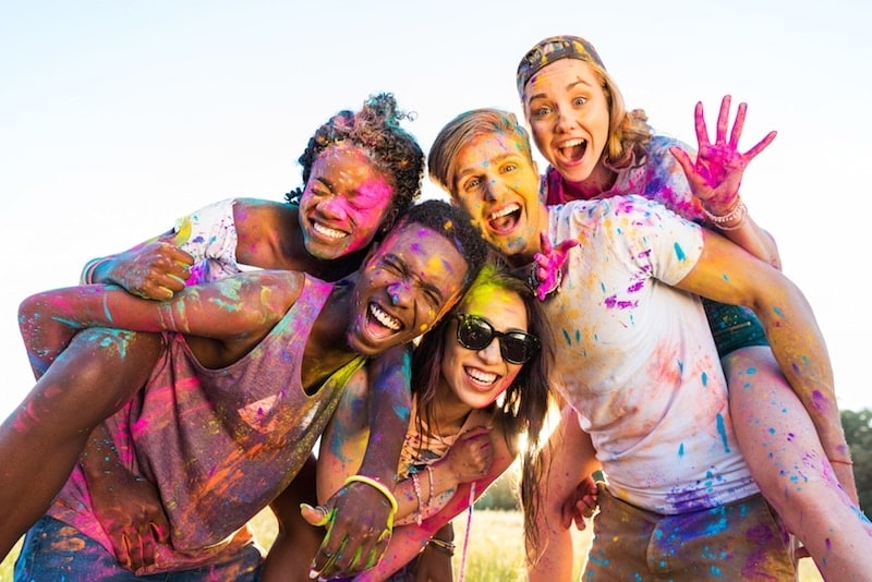 group of smiling friends covered in body paint