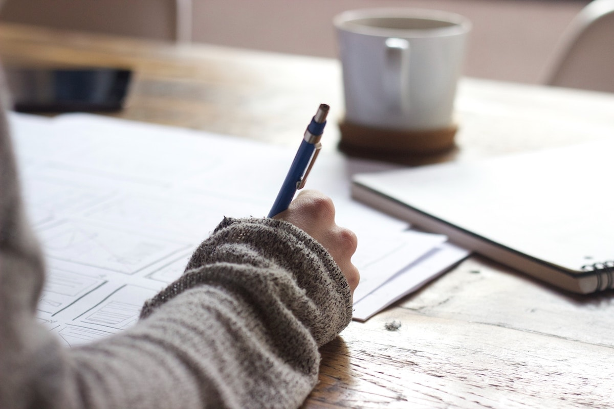 Person writing and drawing sketches on scattered pages on a tabletop, with mug in the background