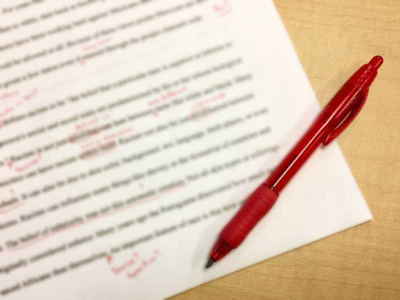 red pen resting on a typed manuscript with red comments and corrections