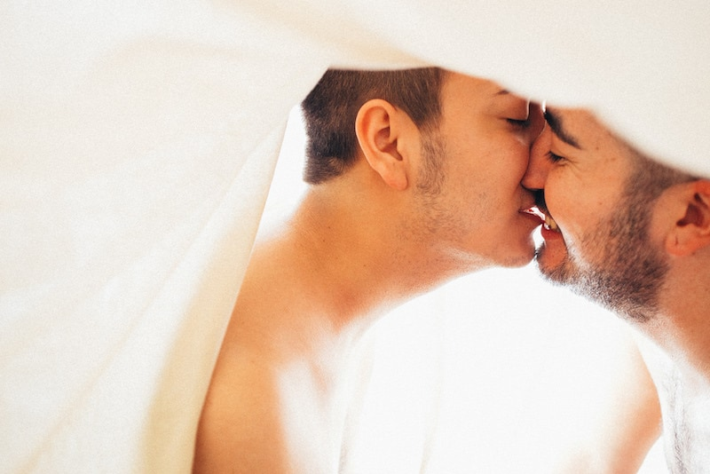 Two men kissing under a white sheet