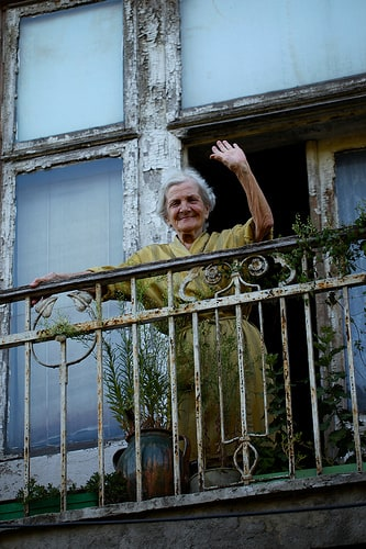 white-haired woma in yellow housecoat waving from balcony