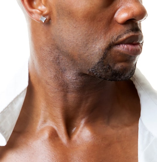 fit bald black man with stud earring and open white shirt exposing six pack abs