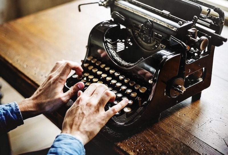 person typing on manual typewriter