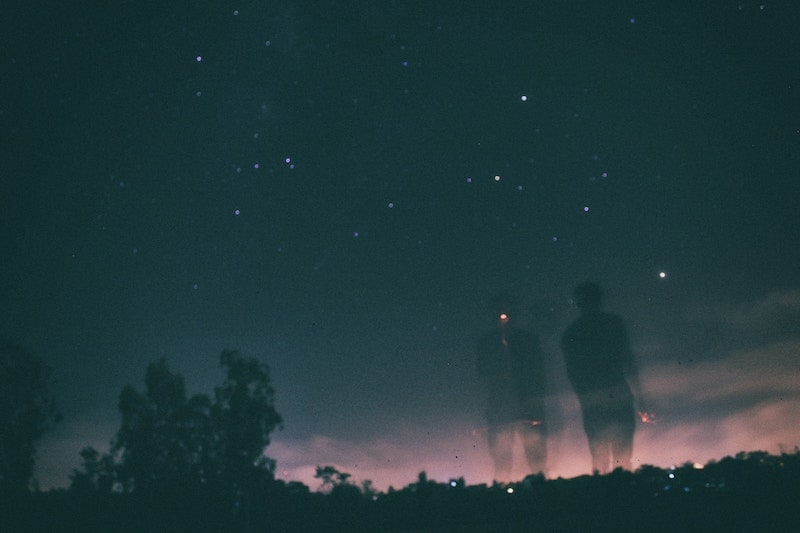ghosly images of human in front of dark sky