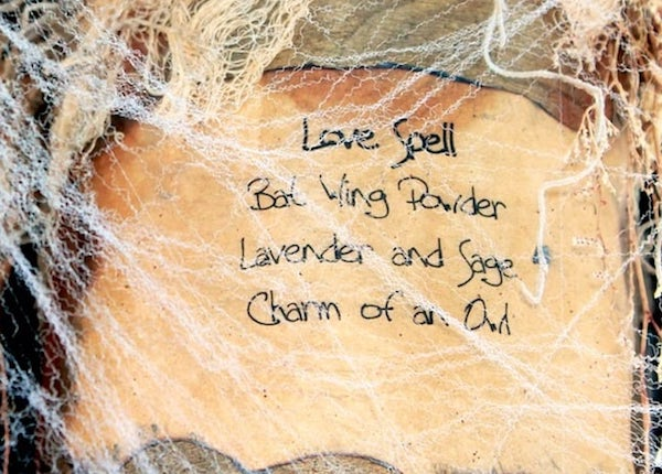 Photo of paper label covered by cobweb that reads Love spell, batwing powder, lavender and sage, charm of an owl