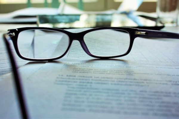 eye glasses resting on a piece of paper filled with typeface