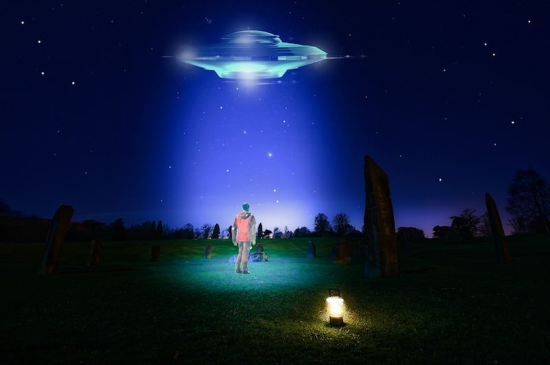 person standing under UFO in beam of light at night. Photo has a peaceful rather than scary tone