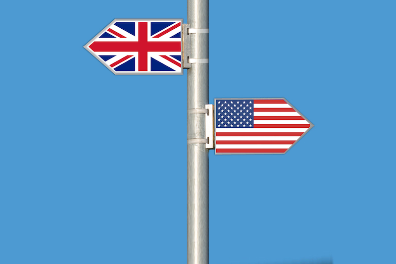 sign post with arrow-shaped signs of uk flag and american flag pointing in opposite directions