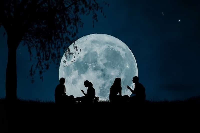 people talking on a summer night with the full moon as a backdrop